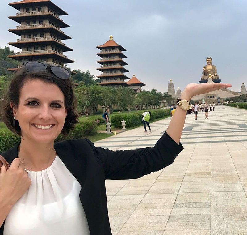 Mitarbeiterin von Gebeco in Asien vor einem Buddha
