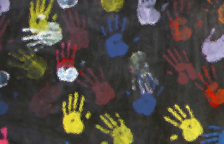 bunte Abdruecke von Kinderhaenden auf schwarzer Leinwand