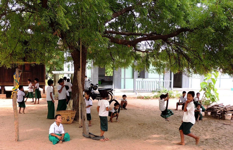 Kinder spielen draussen unter Baum