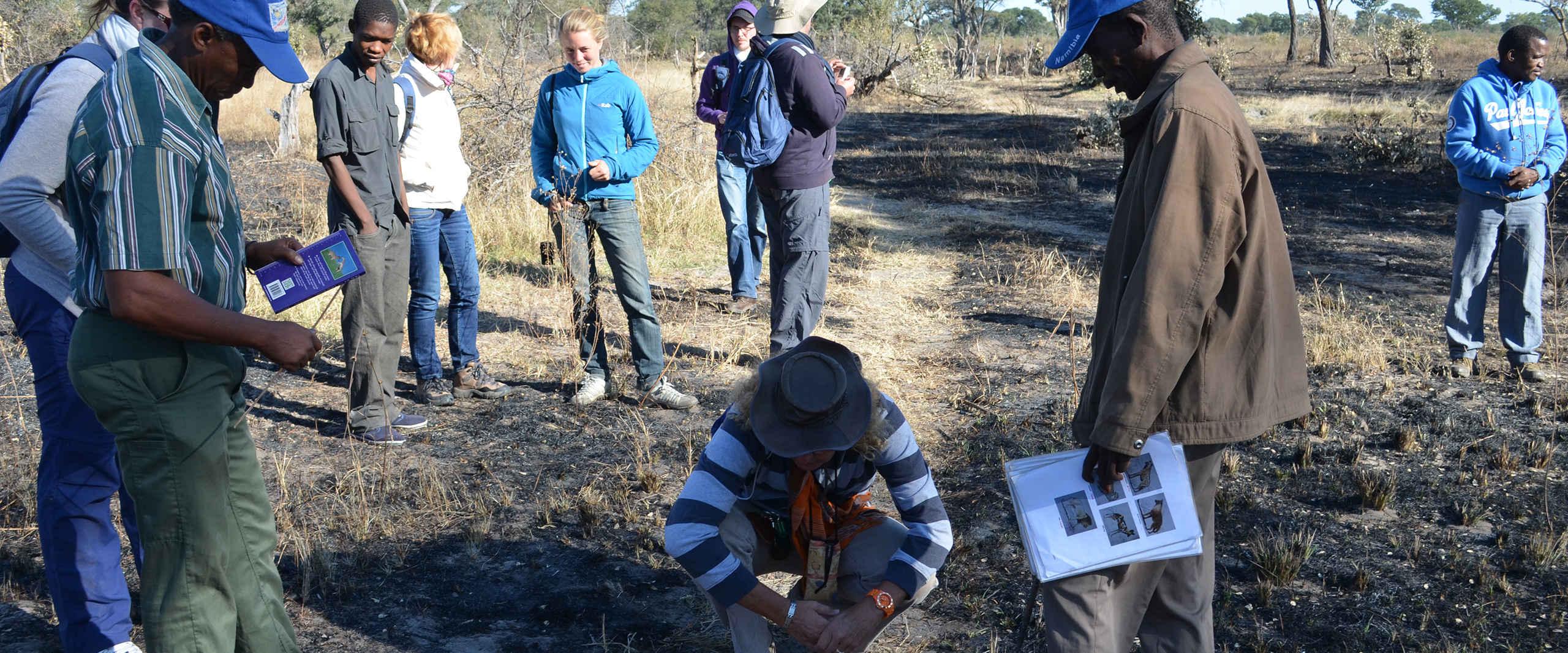 Reisegruppe erlernt Faehigkeiten im Rahmen des Spurenleserprojektes der Khwe