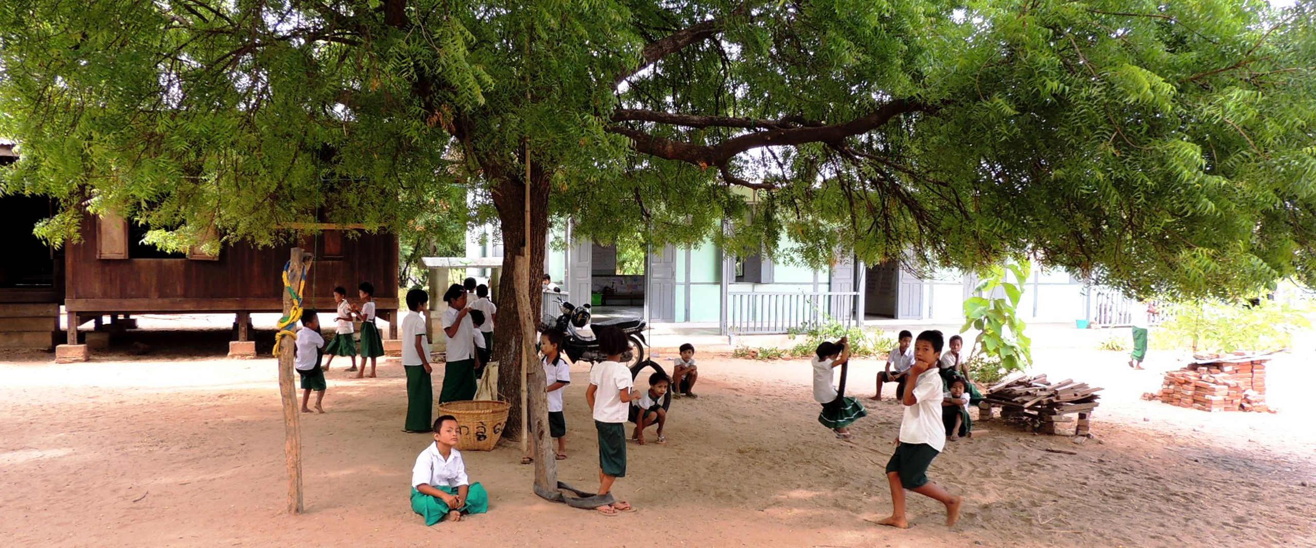 Schueler spielen auf Sandplatz vor der Taung Ba Schule in Myanmar