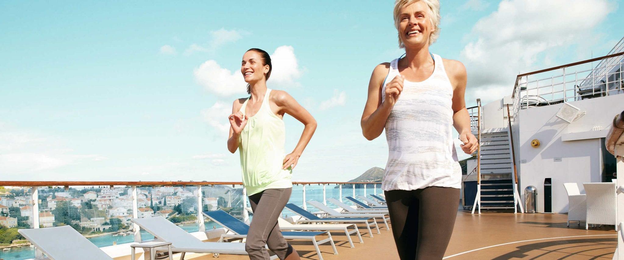 Zwei Frauen joggen an Deck eines Kreuzfahrtschiffes