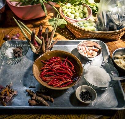 Tisch mit thailaendischem Essen in Schüsseln