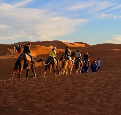 Kamelreiter reiten durch Marrokos Wüste