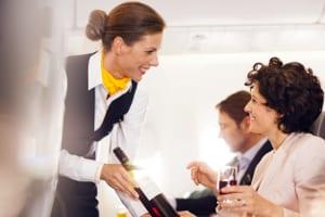 Lufthansa - Stewardess bietet Wein an