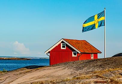 Rotes Holzhaus mit Flagge in Schweden